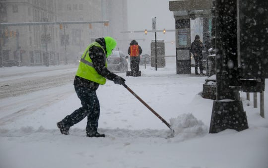 Qline employee Jorge Aguilar shovels snow at the Grand Circus Qline stop as heavy snows hit Metro Detroit Monday, Jan. 28, 2019.