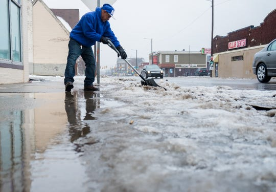 Jesus Perez of Detroit works on shoveling snow in front of Lupita's Wash & Dry on W. Vernor Hwy. in Southwest Detroit as rain melts down snow on Wednesday, January 23, 2019.
