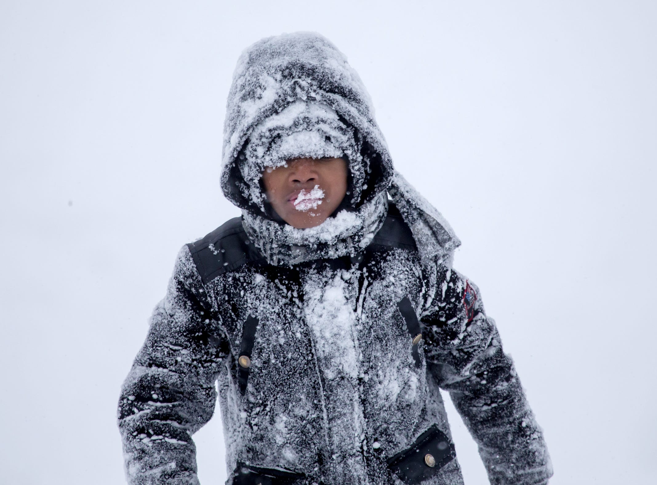 DJ Shackelford of Flint walks up the hill with a mouth full of snow while sledding at Flint Southwestern Academy in Flint on Monday, January 28, 2019.