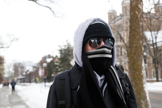 U-M freshman Ian Fiorini is all covered as he walks across University of Michigan central campus in Ann Arbor, Tuesday, Jan. 29, 2019.