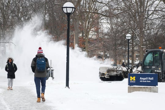 U-M students walks by Angell Hall on central campus as a groundkeeper cleans off the sidewalk with a snow sweeper in Ann Arbor, Tuesday, Jan. 29, 2019.