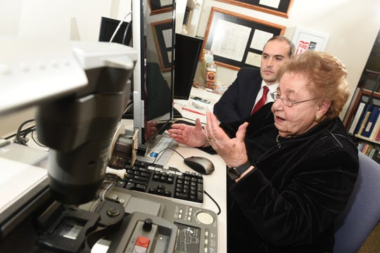 Clara Garbon-Rednoti, a Holocaust survivor, examines and reads documents with attorney Jonathan H. Schwartz using a micro-film machine in the library of the Holocaust Memorial Museum in Farmington Hills on Thursday, January 10, 2019.