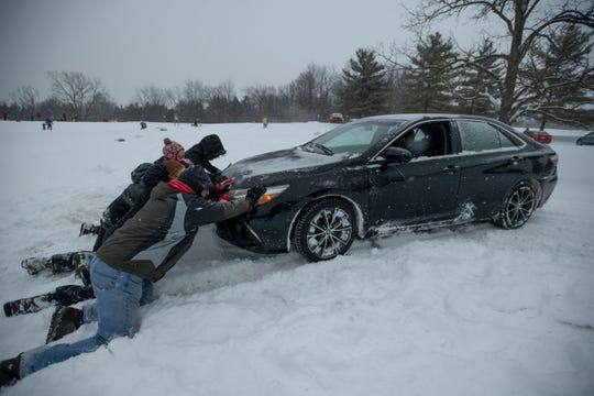 Good Samaritans help push a car owned by Jag Gangishetti of Farmington Hills out of a ditch at Heritage Park in Farmington Hills on Monday.