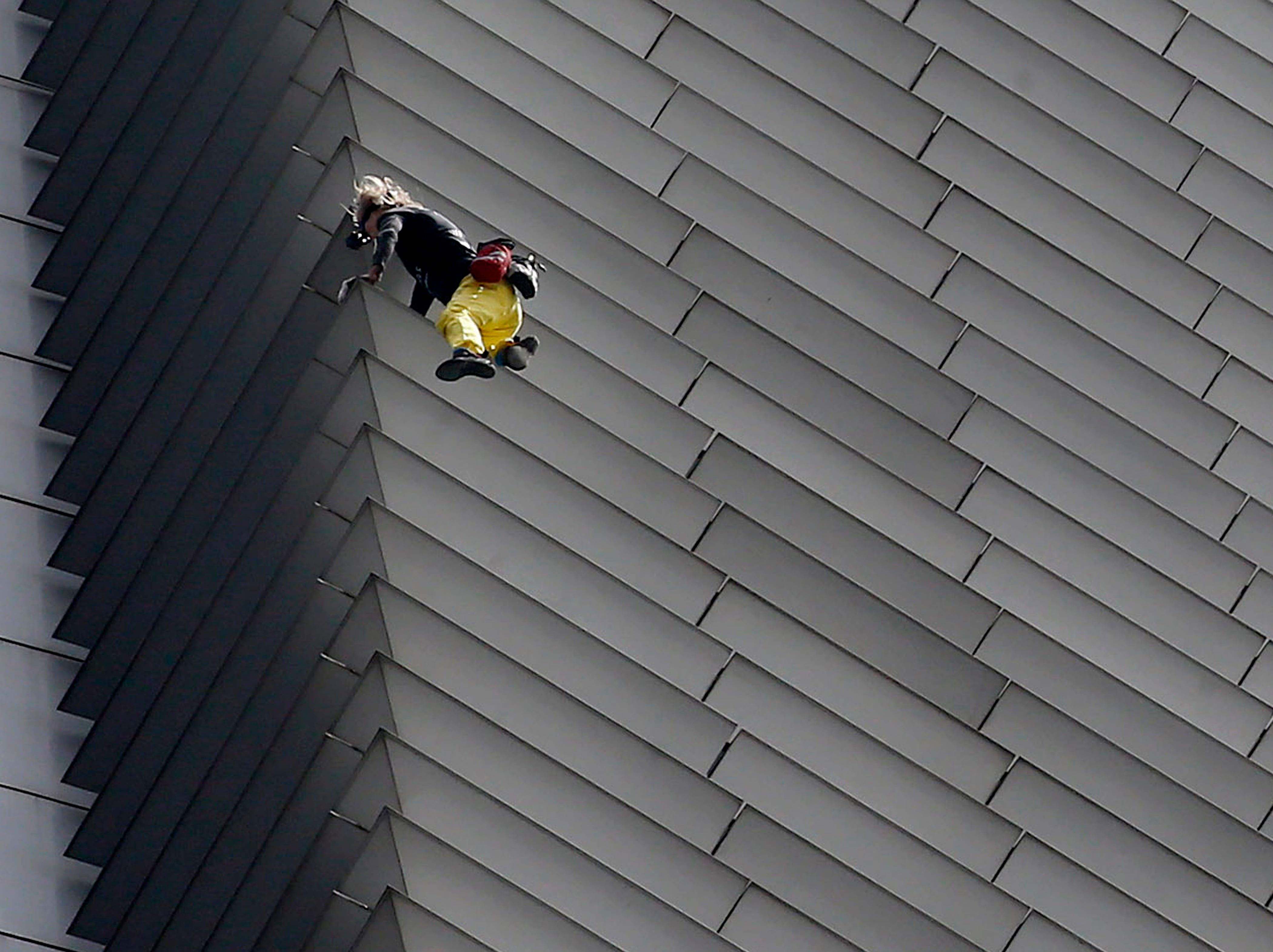"""French urban climber Alaine Robert, popularly known as """"Spiderman"""", climbs the 47-Storey GT Tower Building in Makati, Philippines, Tuesday, Jan. 29, 2019. Robert, who has scaled many skyscrapers and high-rise buildings all over the world, made his Manila climb in less than two hours to the cheers of the crowd below. He was immediately taken into police custody for investigation."""
