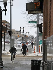 Bundled against the cold, pedestrians and a sandwich shop delivery rider make their way under a sign proclaiming a balmy +7 degrees on Tuesday in downtown Lansing.
