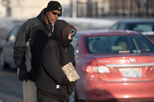 Detroit Rescue Mission Ministries case worker Herbert Morris tries to convince a homeless woman panhandling on Warren Avenue to come to a shelter for the evening, on Wednesday afternoon. The woman refused to go to the shelter despite the fact that the mercury is expected to dip well below zero tonight.
