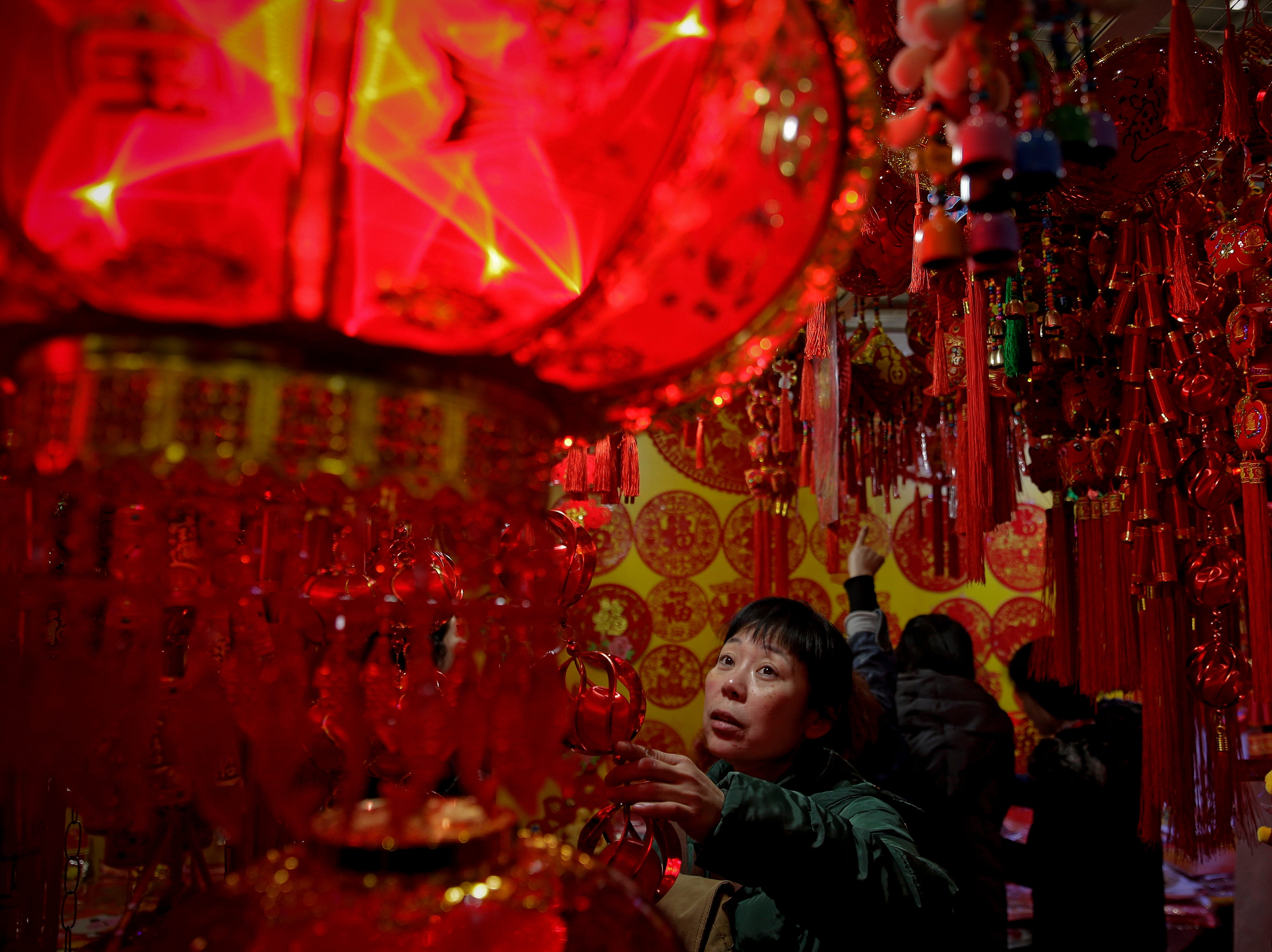 A woman selects Lunar New Year decorations on sale at a market in Beijing, Tuesday, Jan. 29, 2019. China will celebrate Lunar New Year on Feb. 5, which marks the Year of the Pig on the Chinese zodiac.