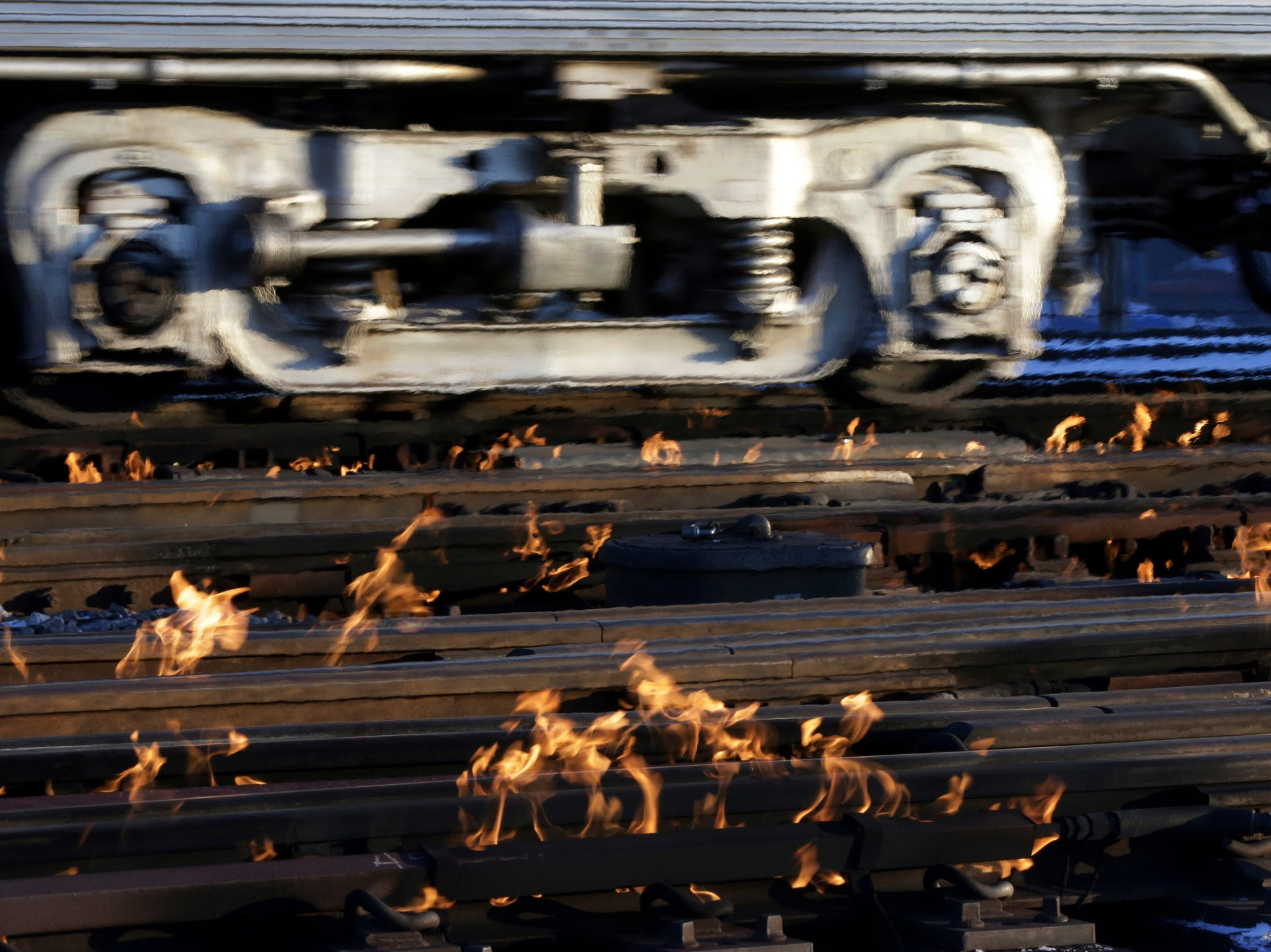 A Metra train moves southbound to downtown Chicago as the gas-fired switch heater on the rails keeps the ice and snow off the switches near Metra Western Avenue station in Chicago, Tuesday, Jan. 29, 2019. Forecasters warn that the freezing weather Tuesday could be life-threatening.