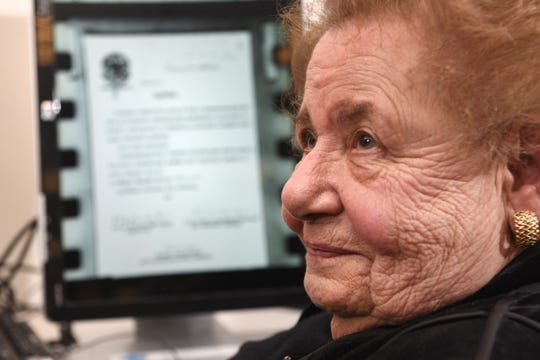 Clara Garbon-Rednoti, a Holocaust survivor, examines and reads documents on micro-film in the library of the Holocaust Memorial Museum in Farmington Hills.