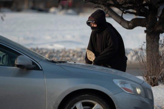 A homeless woman panhandles on Warren Avenue in Detroit, Jan. 29, 2019.