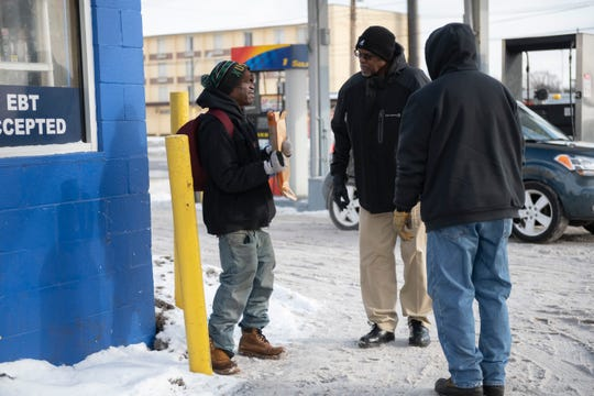 Case worker Herbert Morris, center, and transportation manager Michael Colbert, right, ask a homeless man named Danny to come with them to a Detroit Rescue Mission Ministries shelter, while panhandling at a gas station at Harper and Connor, in Detroit, January 29, 2019.  Danny refused to go to the shelter.