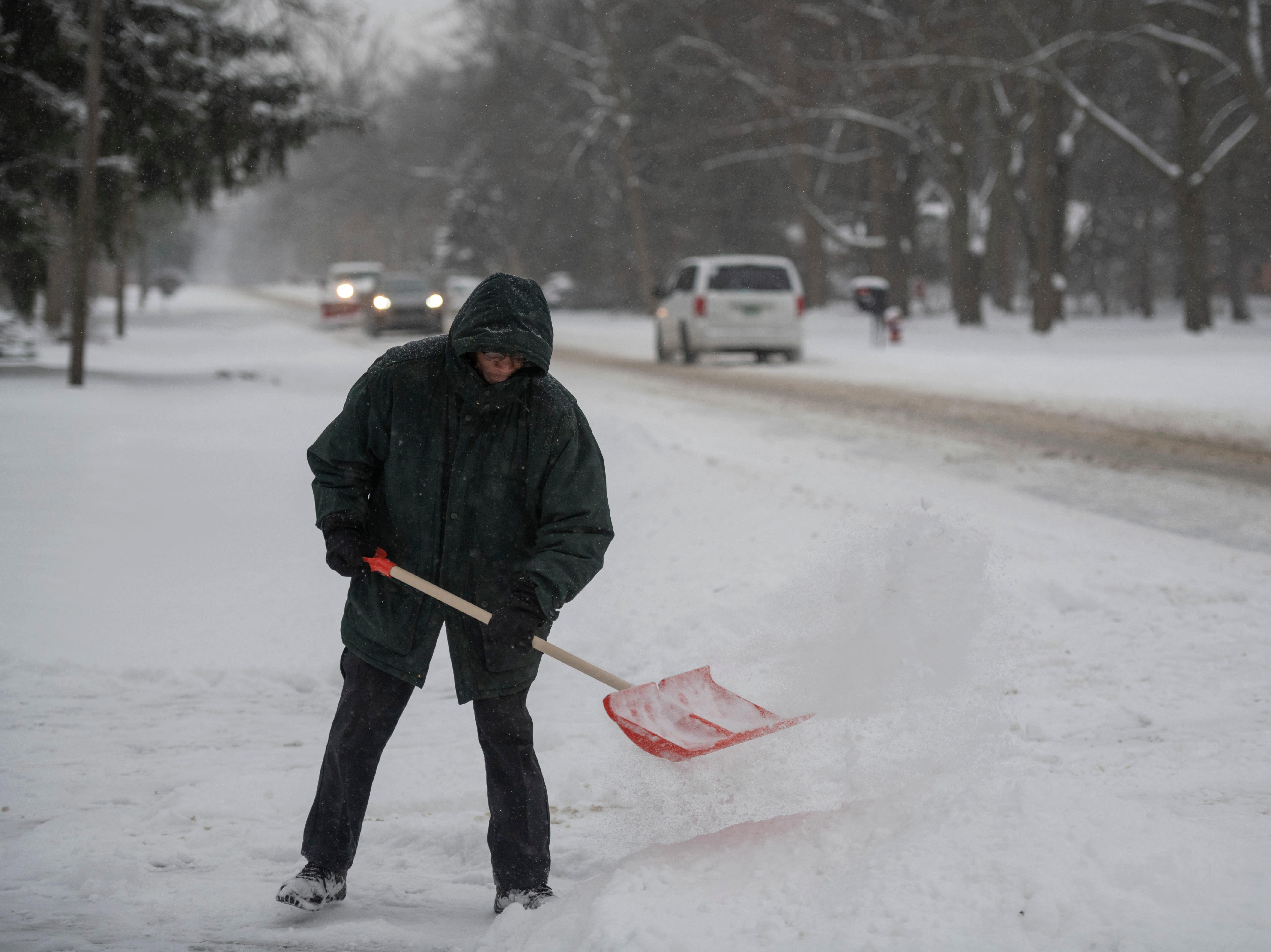 Dayle King shovels the driveway in front of his home on Berg Road, in Southfield.