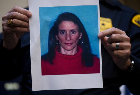 A Houston Police officer holds up the photo of one of the suspects,  Rhogena Nicholas, during a news conference.