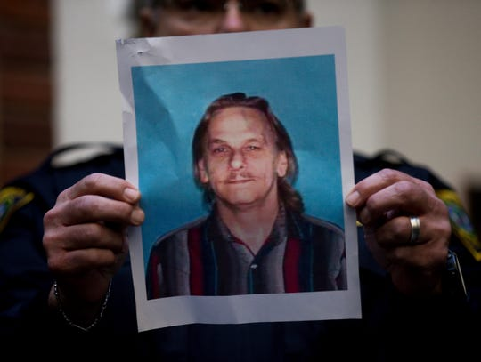 A Houston Police officer holds up the photo of one of the suspects , 59-year-old Dennis Tuttle, during a news conference.