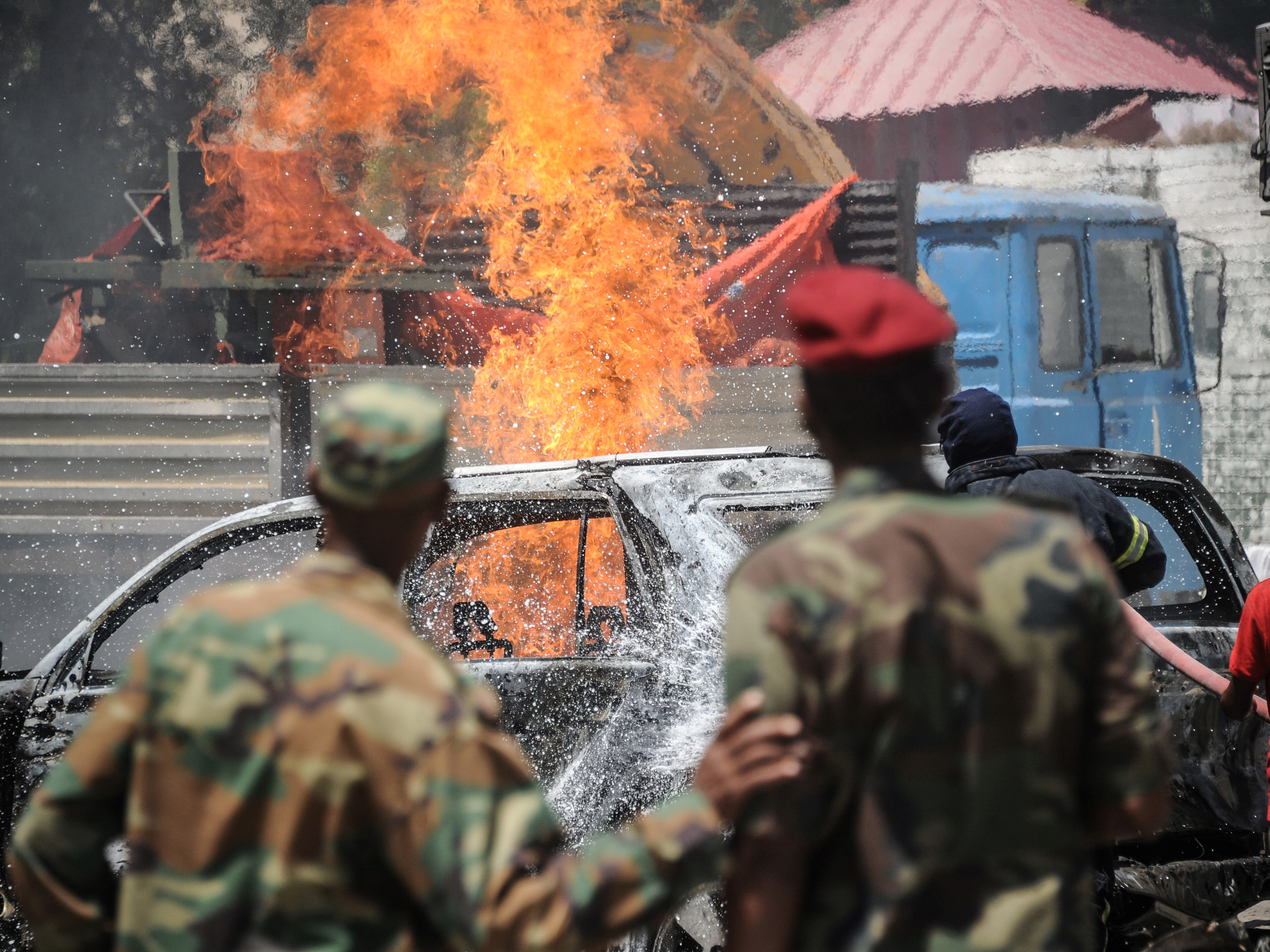 Firefighters try  to extinguish a fire at the scene of a car bombing in Mogadishu, Somalia, on January 29, 20 19.  Two people were killed and five wounded when a car packed with explosives was detonated near the ministry of petroleum in the Somali capital, a security official said.