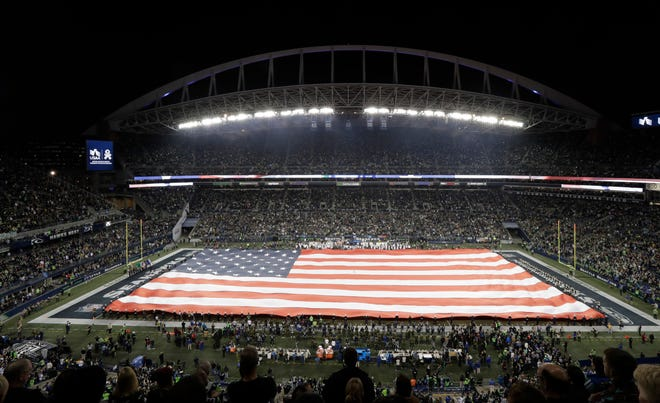 A full-field U.S. flag is displayed at CenturyLink Field before an NFL football game between the Seattle Seahawks and the Green Bay Packers, Thursday, Nov. 15, 2018, in Seattle as part of the NFL's Salute to Service campaign to honor members of the military. (AP Photo/Stephen Brashear)