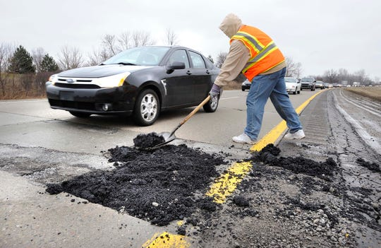 CAPTION INFORMATION. An Oakland Co. Road Commission worker, who preferred not to give his name, fills a large pothole on I-59 westbound just east of Crooks Road. Potholes cause flat tires along I-59, between Crooks and Livernois in Rochester Hills, Michigan on February 12, 2009.  Images by Daniel Mears / The Detroit News. _