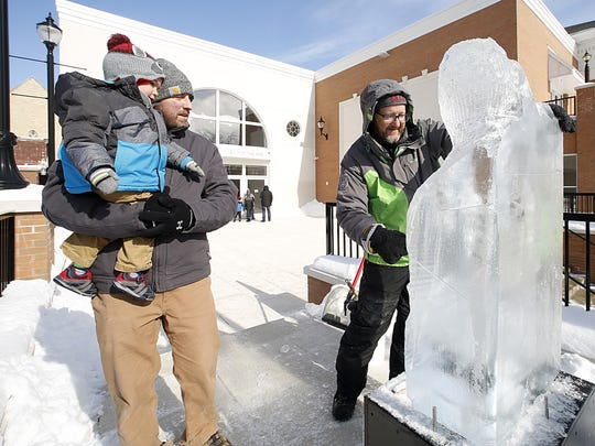 Rhett and Ken Gardner of Fond du Lac watch Greg Moerner of Milwaukee make an ice sculpture on Feb. 10, 2018, in front of the Thelma Center for the Arts in downtown Fond du Lac. The sculptures were part of Sturgeon Spectacular which is a winter festival in Fond du Lac that coincides with the opening of sturgeon spearing season.