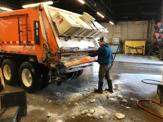 Fond du Lac County Highway Department worker Tyler Thielke clears chunks of frozen salt from a plow. The frozen salt clogs up the augers and doesn't work when temperatures get this cold, said Fond du Lac Colunty Highway Commissioner Tom Janke. He is warning area residents the roads are slippery and ice-covered.