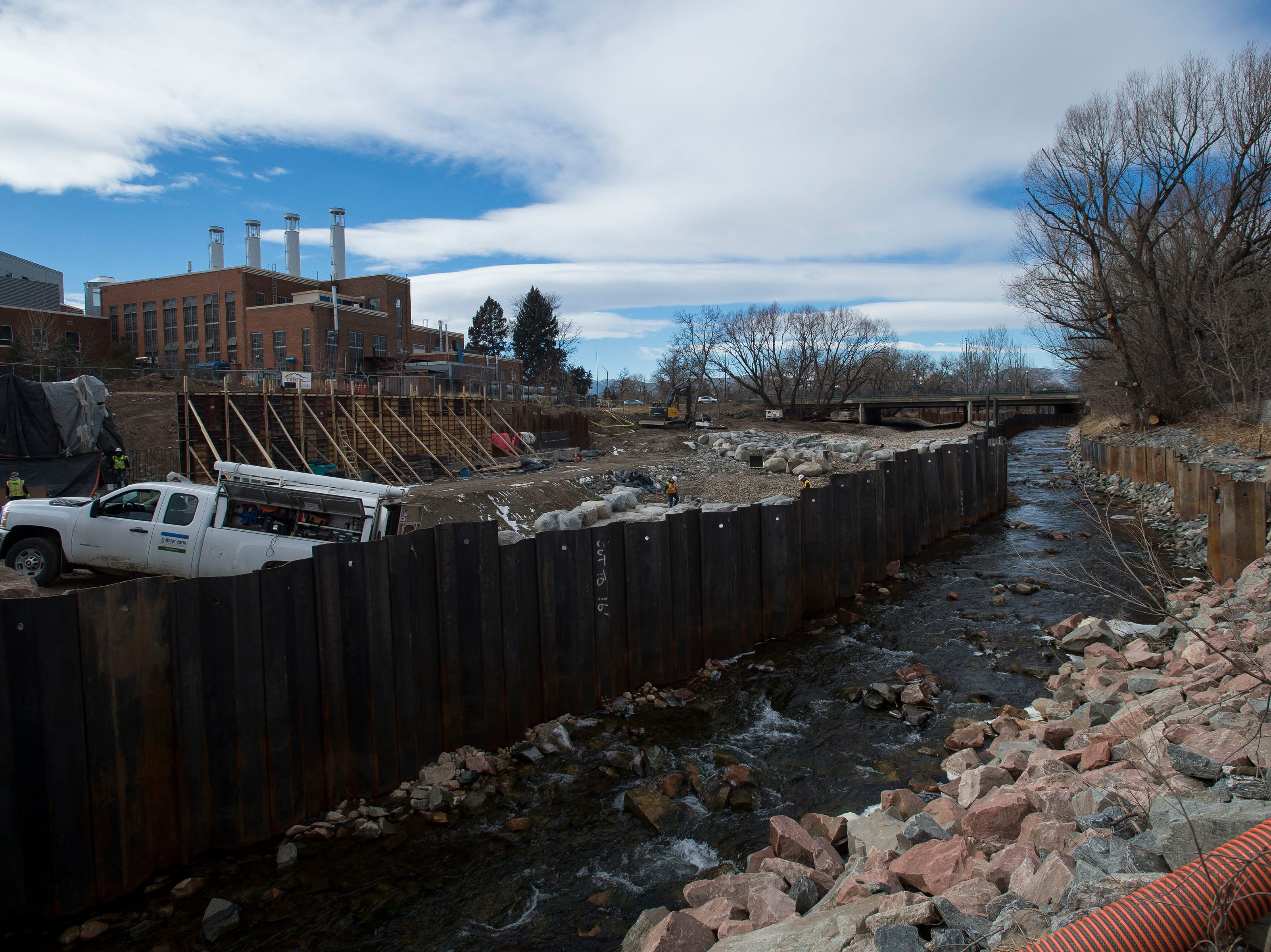 The low-running river is diverted from the area under construction while construction crews build out the South side of the whitewater park on Wednesday, Jan. 23, 2019, on the Cache la Poudre River, just South of North College Avenue in Fort Collins, Colo.