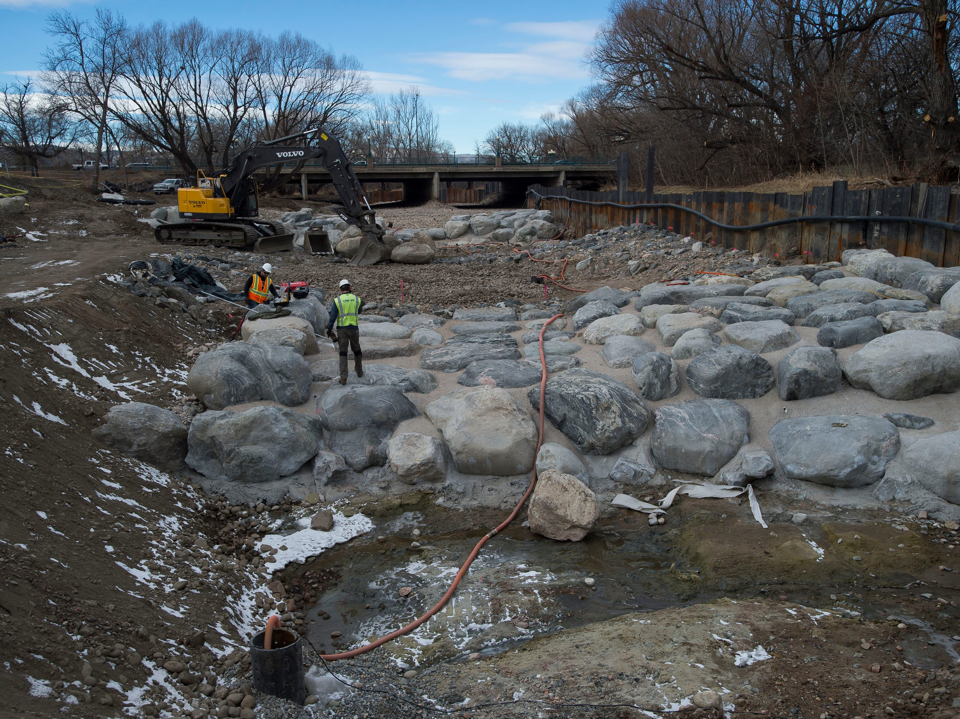 Construction crew work on-site where two concrete and stone wave features, complete with small passages for fish to move freely, have been built into the riverbed on Wednesday, Jan. 23, 2019, on the Cache la Poudre River, just South of North College Avenue in Fort Collins, Colo.