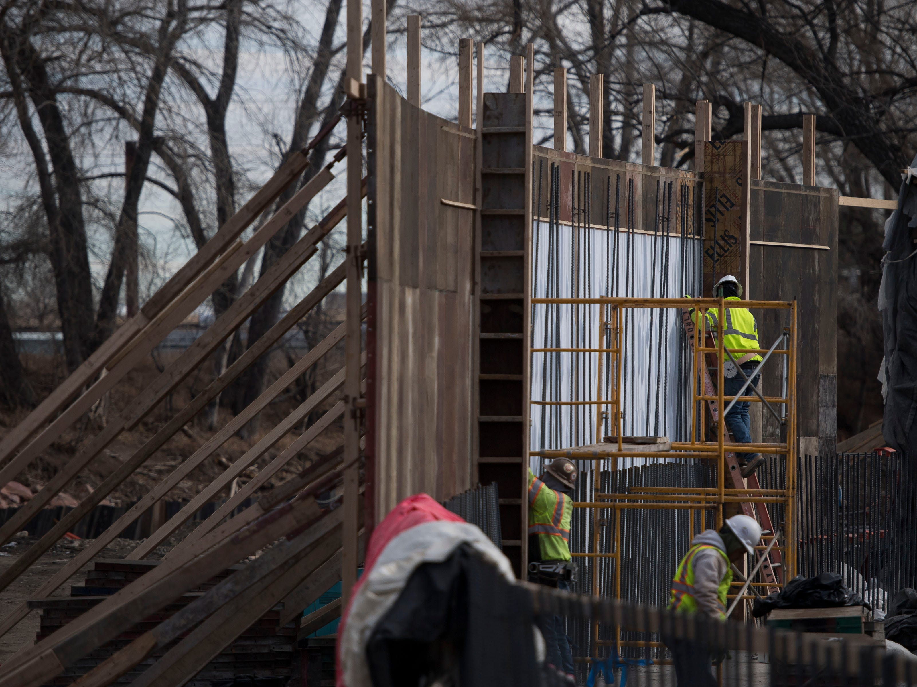 Construction crews build a concrete form on the South bank of the river on Wednesday, Jan. 23, 2019, on the Cache la Poudre River, just South of North College Avenue in Fort Collins, Colo.