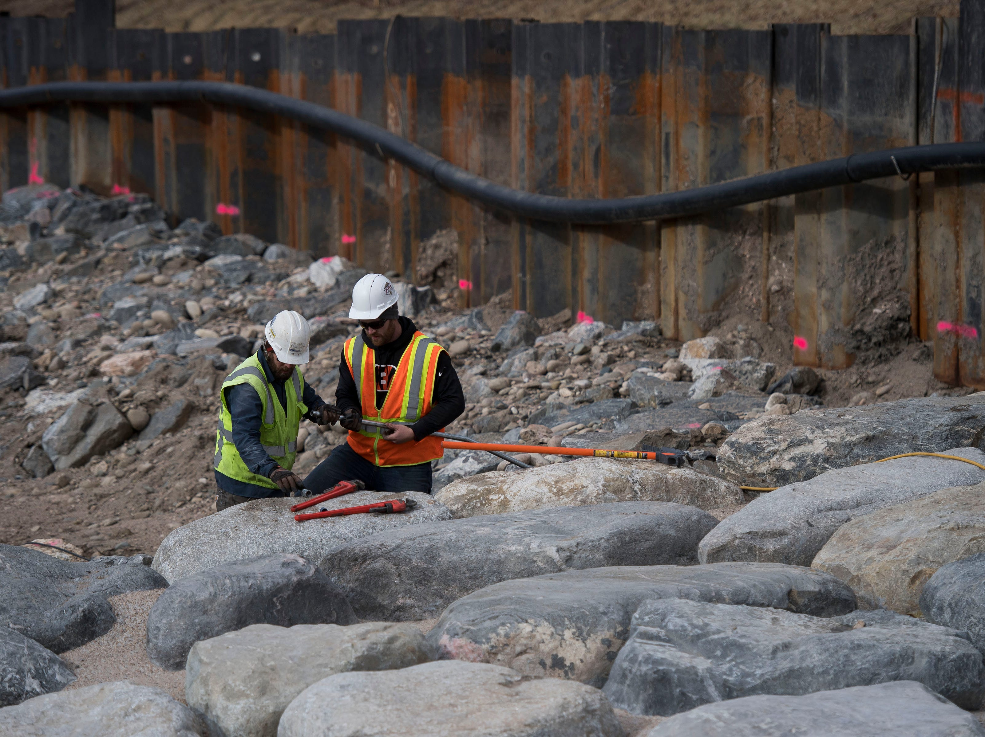Water & Earth Technologies, Inc. project engineers Erik Carlson and Eric Hess work to install a new flow meter at the base of a wave feature on the riverbed of the river on Wednesday, Jan. 23, 2019, at the future site of the Poudre River Whitewater Park just South of North College Avenue in Fort Collins, Colo.