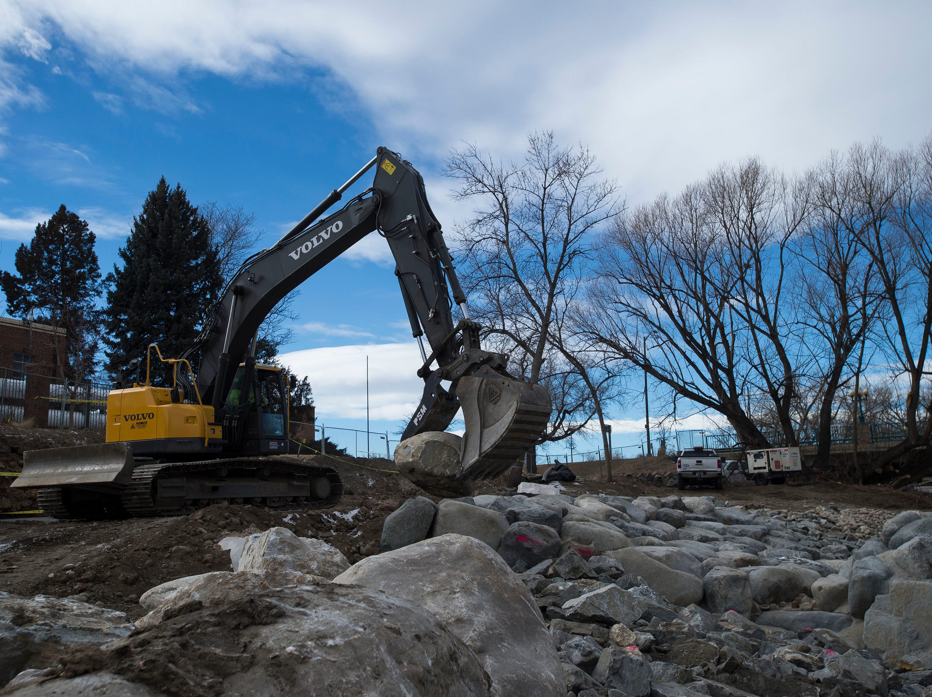 A backhoe drops large rocks into place on the riverbed on Wednesday, Jan. 23, 2019, on the Cache la Poudre River, just South of North College Avenue in Fort Collins, Colo.