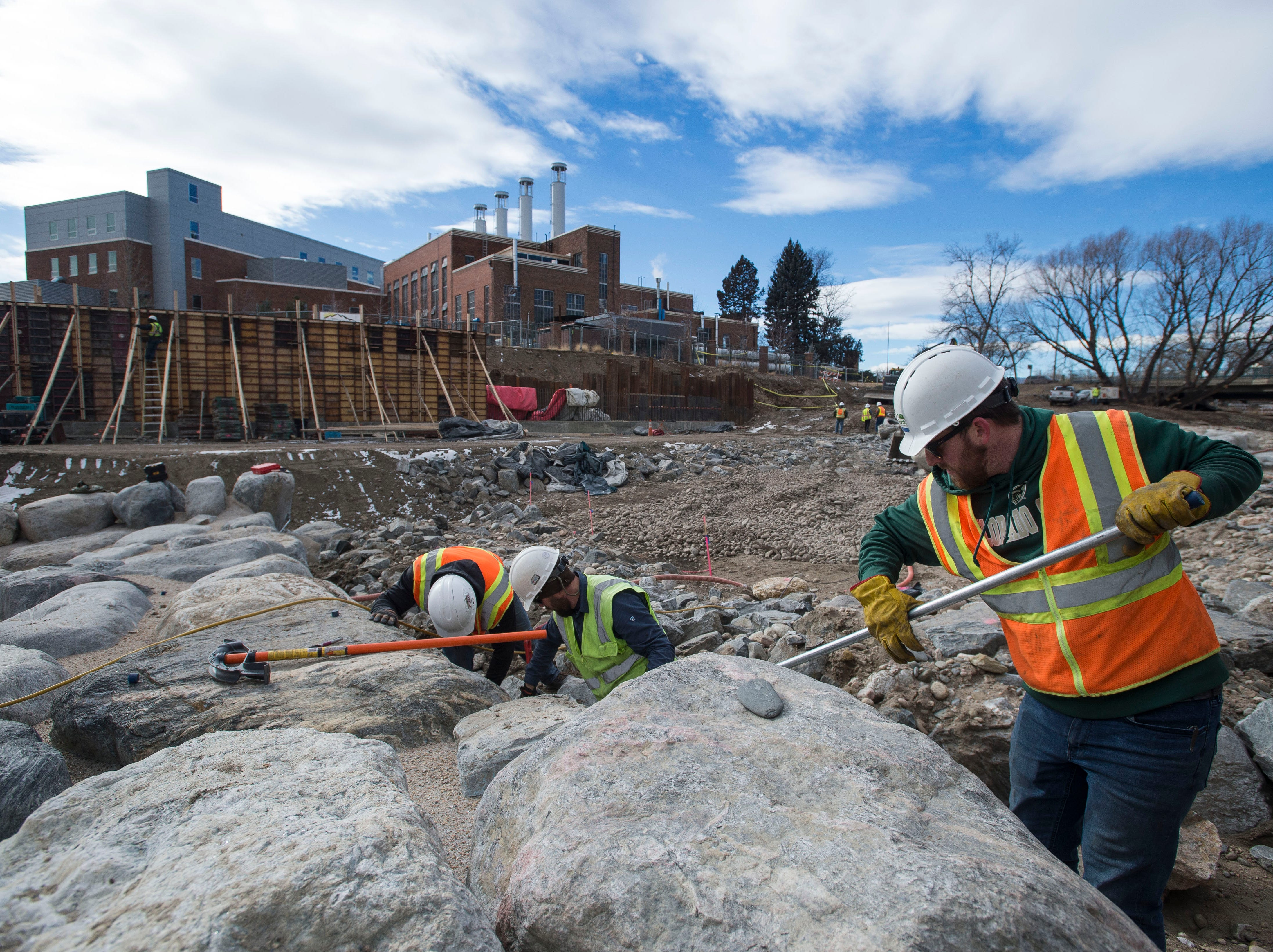 Water & Earth Technologies, Inc. project engineers, from right, Keller Smith, Erik Carlson and Eric Hess work to install a new flow meter at the base of a wave feature on the riverbed of the river on Wednesday, Jan. 23, 2019, at the future site of the Poudre River Whitewater Park just South of North College Avenue in Fort Collins, Colo.