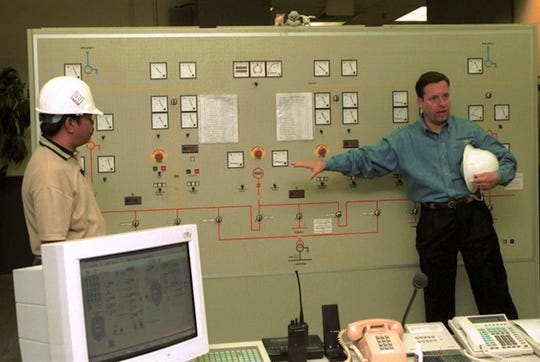 In this March 2001 file photo, Frederick LaCroix, right, general manager of Marianas Energy Company, talks about the control center of the company's power plant in Piti. The plant, which was built and operated by MEC to supplement the islandwide power system, was transferred to the Guam Power Authority, effective Tuesday, but still will be operated and maintained by MEC for at least five years.