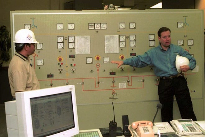 In this March 2001 file photo, Frederick LaCroix, right, general manager of Marianas Energy Company, talks about the control center of the company's power plant in Piti. The plant, which was built and operated by MEC to supplement the islandwide power system, was transferred to the Guam Power Authority in January 2019.
