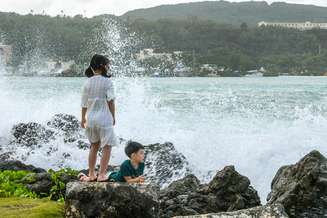 Kids brave the ocean spray, created by waves crashing on the rocky shore of the Paseo in Hagåtna, on Tuesday, Jan. 29, 2019.