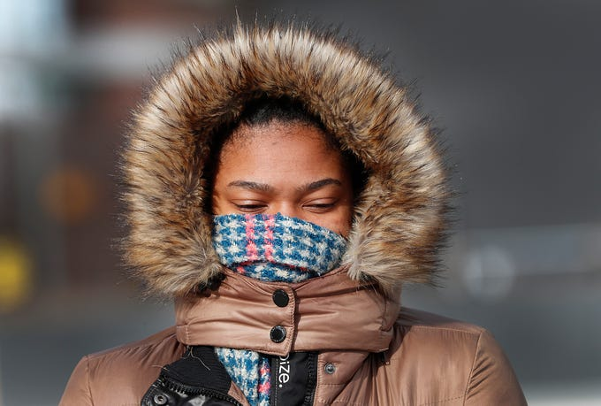 Asia Brannon attempts to keep warm while walking to the at the Julia M. Carson Transit Center to catch her bus Tuesday, Jan. 29, 2019.