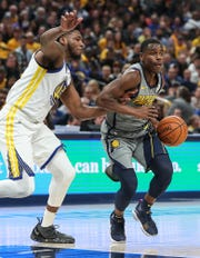 Golden State Warriors forward Marcus Derrickson (32)closely guards Indiana Pacers guard Aaron Holiday (3) in the first half of the game at Banker's Life Fieldhouse in Indianapolis, Monday, Jan. 28, 2019.