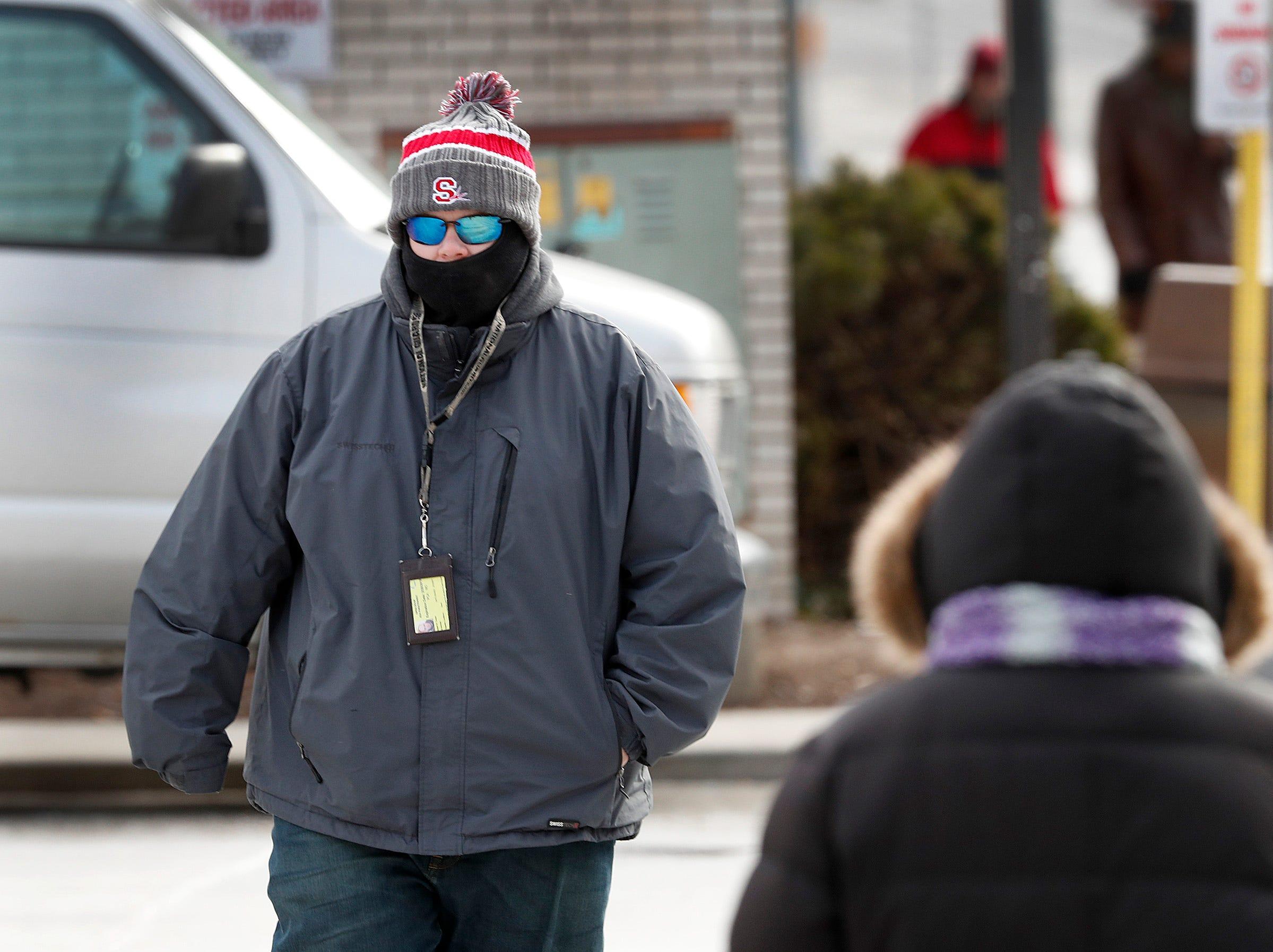 Pedestrians attempt to keep warm while walking near the Julia M. Carson Transit Center Tuesday, Jan. 29, 2019.