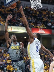 Indiana Pacers guard Edmond Sumner (5) shoots a layup past Golden State Warriors center Kevon Looney (5) in the first half of the game at Banker's Life Fieldhouse in Indianapolis, Monday, Jan. 28, 2019.