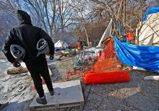 A man holds two warm blankets given to him by officers from the IMPD homeless unit at a homeless camp near the White River on Jan. 29, 2019.