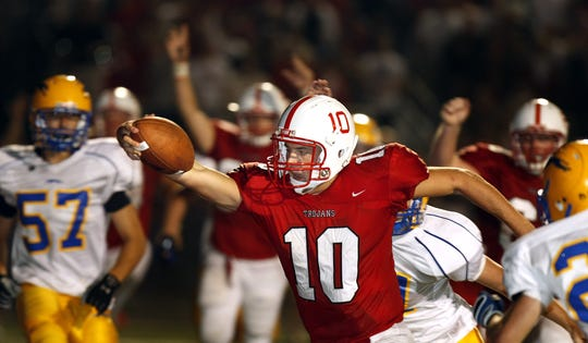 Center Grove QB Jordan Luallen reaches the ball over the goal line for a fourth-quarter touchdown against Carmel in 2008.