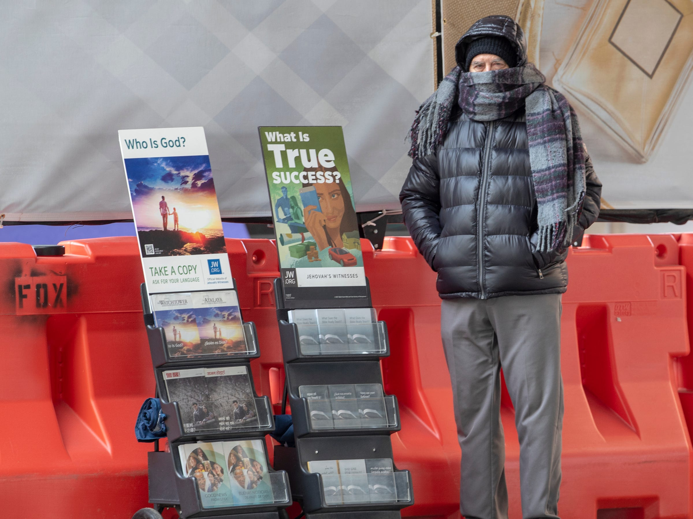 A man works a Jehovah's Witness kiosk in downtown on a cold day of about 15 degrees in central Indiana, Indianapolis, Tuesday, Jan. 29, 2019. The man, who declined to give his name, said he's from Michigan, so he's not bothered much by the cold.