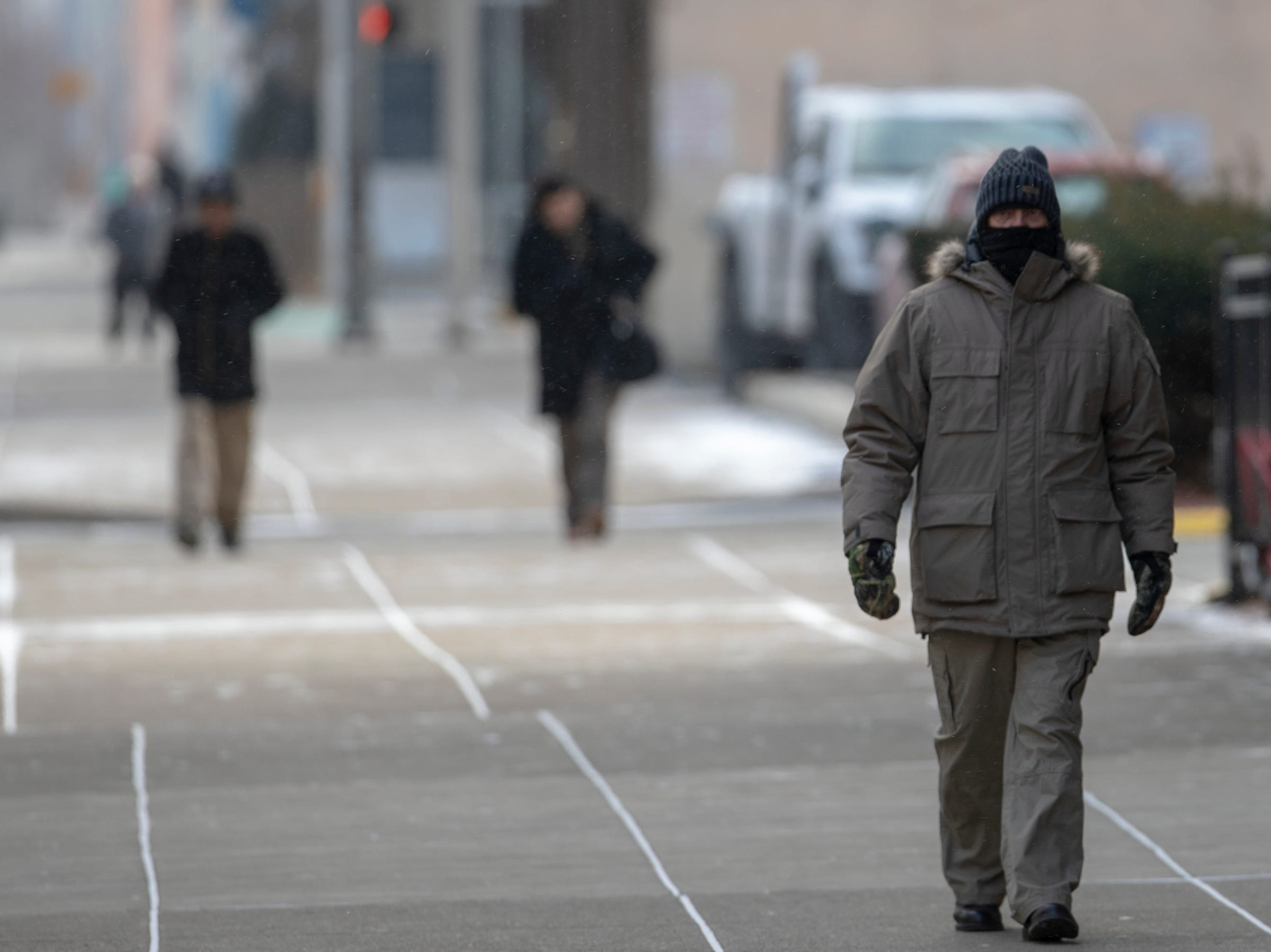 Downtown walkers bundle up on a cold day of about 15 degrees in central Indiana, Indianapolis, Tuesday, Jan. 29, 2019. Temperatures are expected to trend colder tomorrow, with more than ten below zero possible.