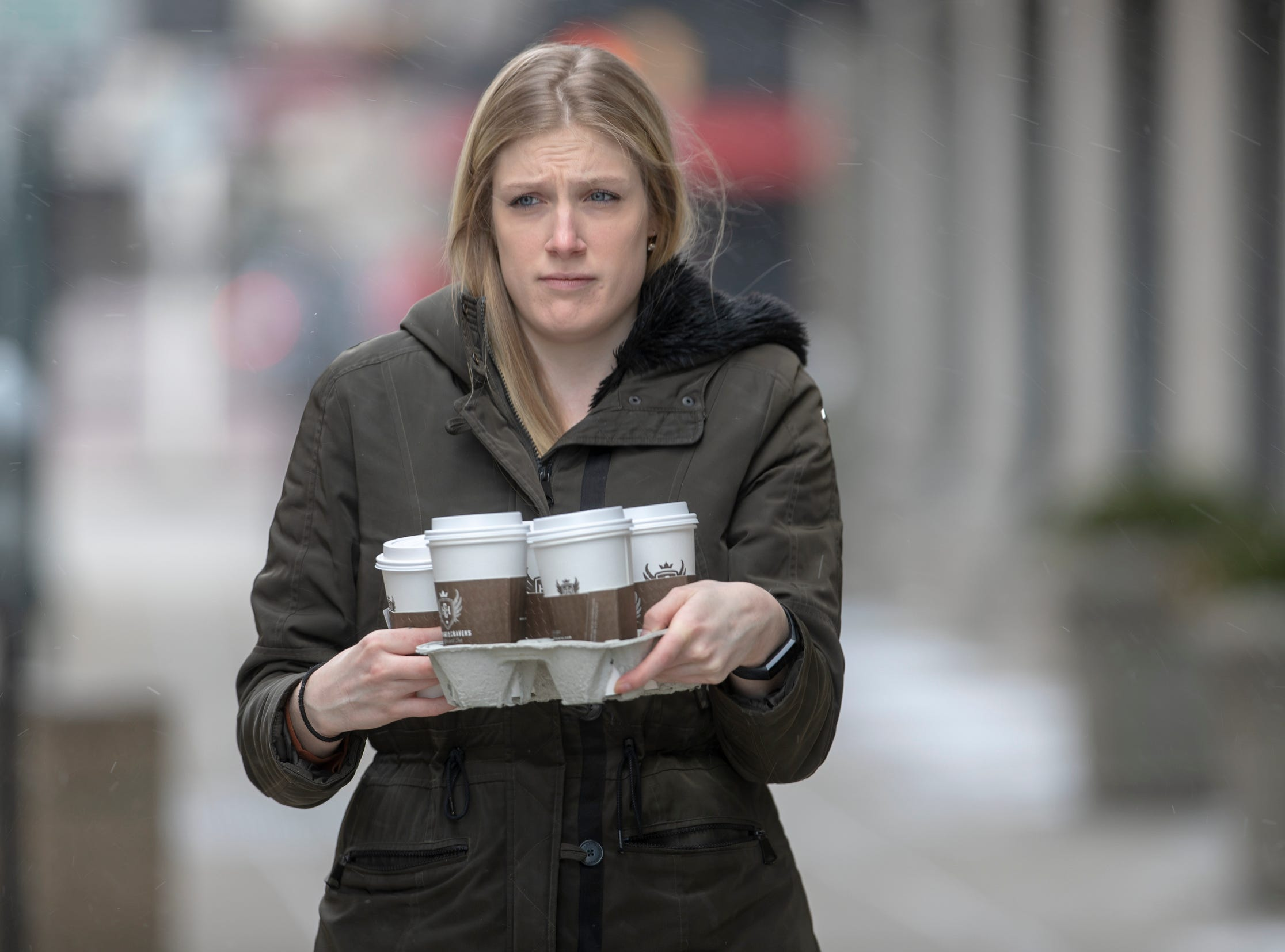 Courtney Kronzer makes a coffee run on a cold day of about 15 degrees in central Indiana, Indianapolis, Tuesday, Jan. 29, 2019. Kronzer, originally from Virginia, said her hands aren't doing too well during the half-block walk from the coffee shop to her office.