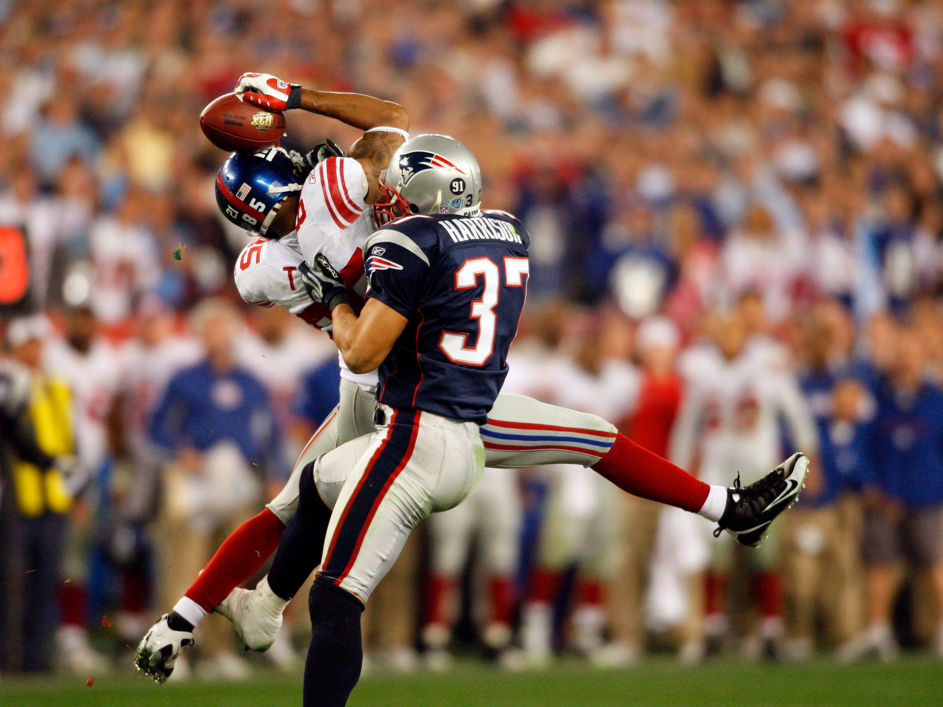 "The Patriots went to Super Bowl XLII with an undefeated season. They were about to match the '72 Dolphins, but were denied that feat by what is considered the greatest Super Bowl play of all time. The New York Giants were losing 14-10, and with 1:15 left on the clock QB Eli Manning threw the ball 32 yards to WR David Tyree. Tyree made ""the helmet catch"" and secured the Giants position that allowed them to score a touchdown and win the game. (pictured: Feb, 3, 2008; Glendale, AZ, USA; New York Giants wide receiver David Tyree (85) hauls in a catch to sustain the game winning drive defended by New England Patriots defensive back Rodney Harrison (37) in Super Bowl XLII at University of Phoenix Stadium. The Giants defeated the Patriots 17-14.)"