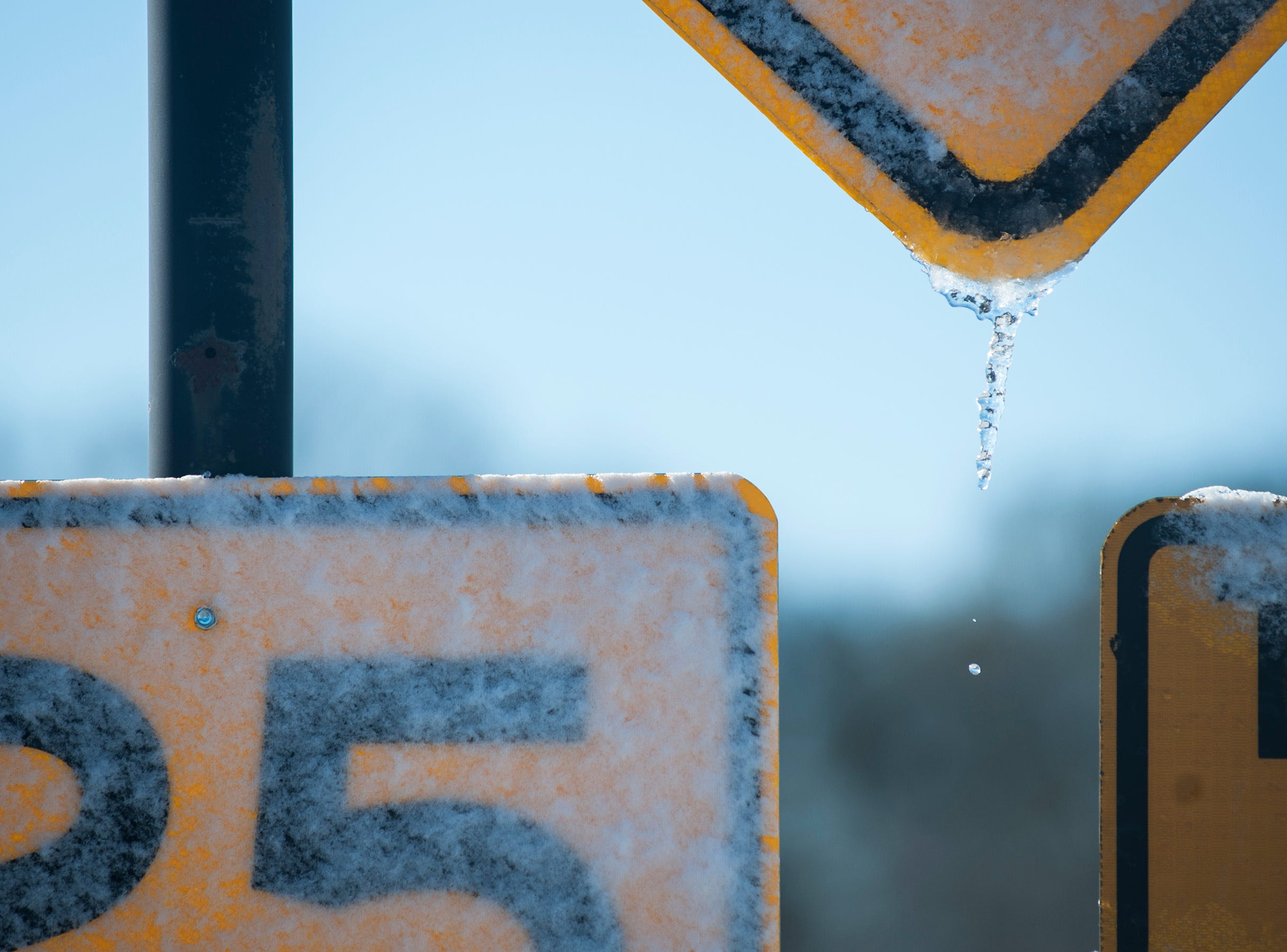 Melting snow on traffic signs in Madison, Miss. and  freezing temperatures are all that remain Tuesday, Jan. 29, 2019, after a cold front moved through state leaving the Jackson, Miss. metro area with less than an inch of snow.