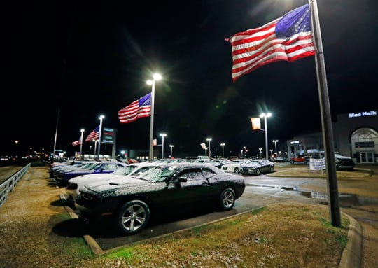 A brisk wind snaps the U.S. flags that line this automotive sales lot in north Jackson, Miss., Tuesday, Jan. 29, 2019.  The National Weather Service has a winter storm warning in effect for parts of central Mississippi including Vicksburg, Jackson and Columbus.