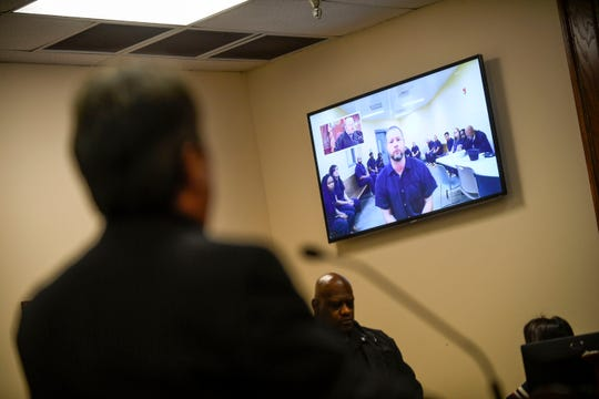 John David Robison appears on a monitor while his attorney Colin Morris stands and speaks for him at the arraignment for Robison at Jackson City Court in Jackson, Tenn., on Tuesday, Jan. 29, 2019.
