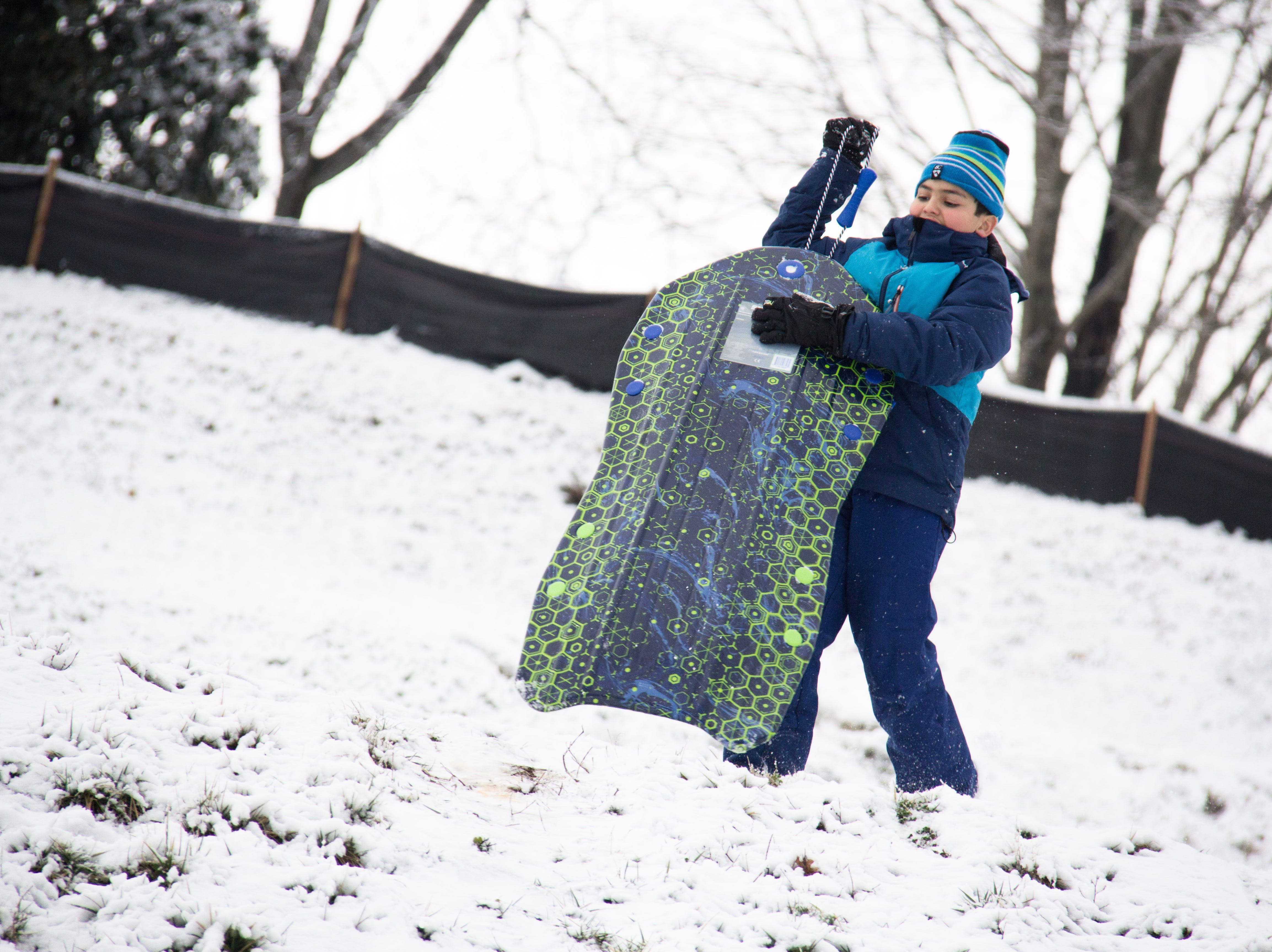 Nine-year-old Ian lugs his sled back tot the top of a hill at Lakeshore Park in Knoxville on Jan. 29, 2019.