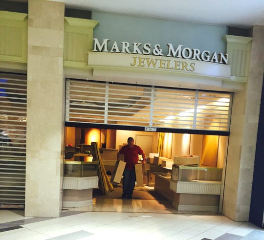 Workers disassemble and remove cases at Marks & Morgan Jewelers at West Town Mall on Monday, Jan. 19, 2019. The store has closed.