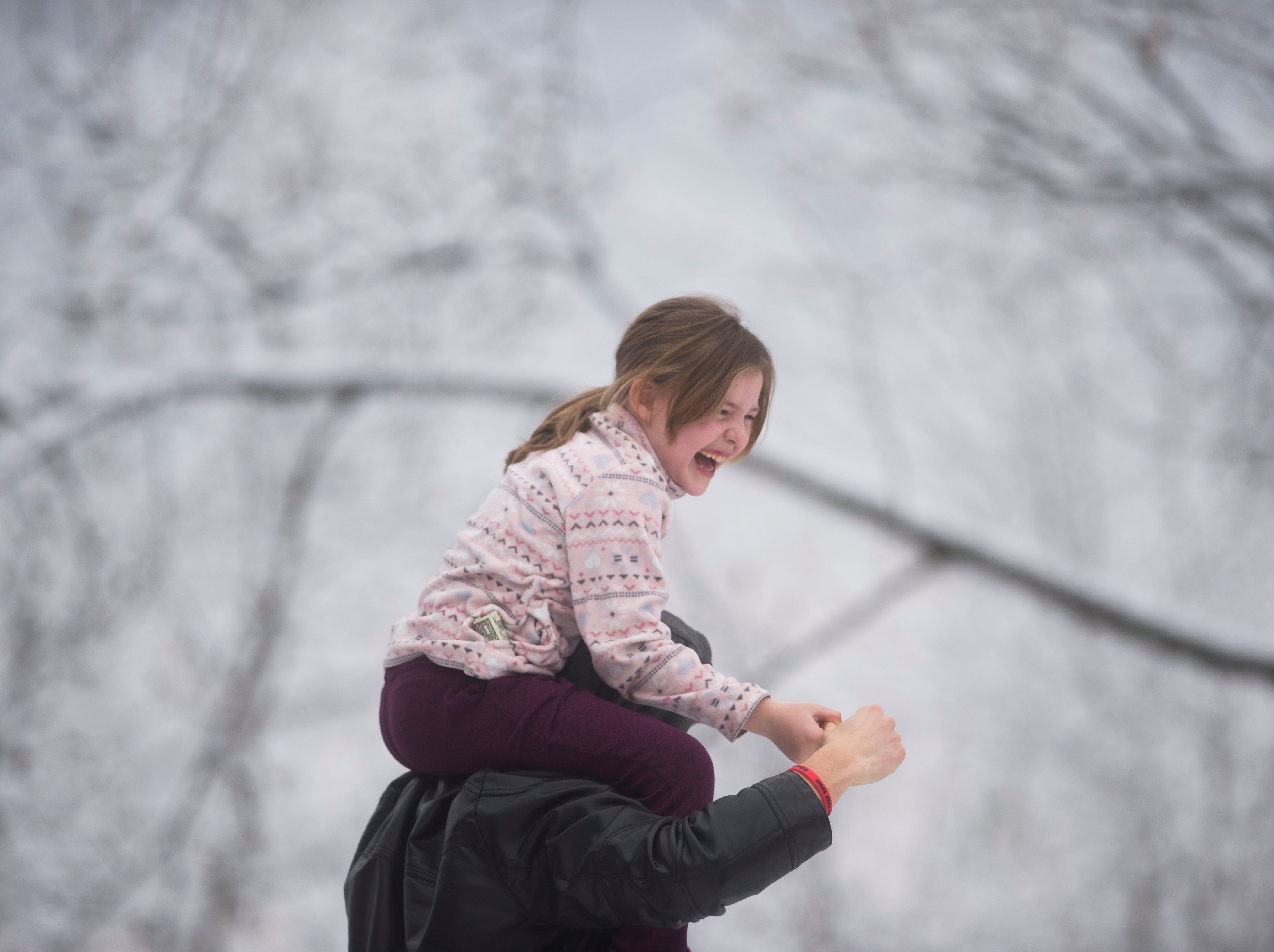 Leeland Robbins, 8, of Knoxville, sits on Clay Rhea's shoulders, on top of Sharps Ridge in North Knoxville Tuesday, Jan 29, 2019. The Knoxville area received about an inch of snow.