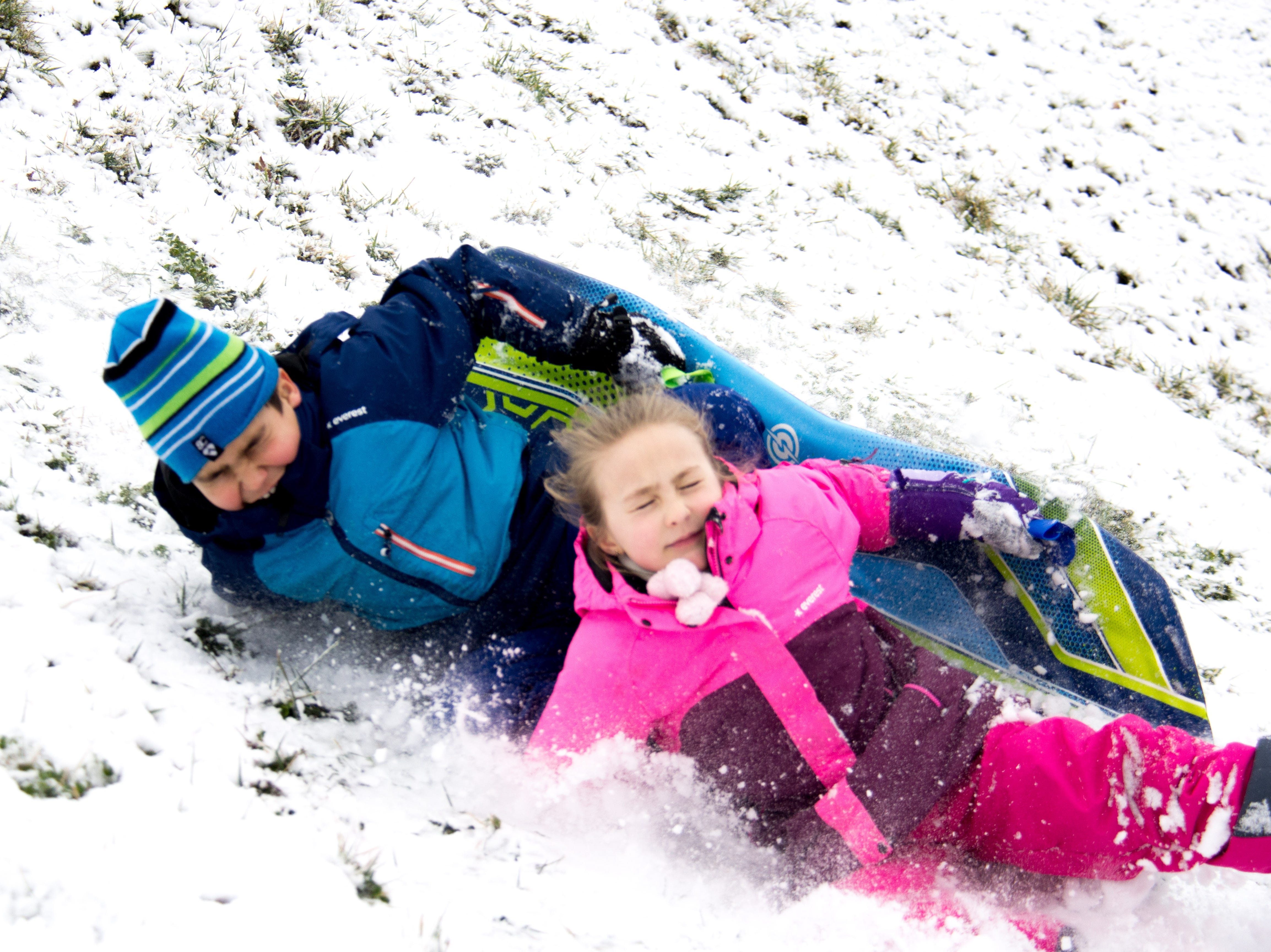 Ian, 9, and 5-year-old Isabella wipe out while sledding down a hill at  Lakeshore Park in Knoxville on Jan. 29, 2019.