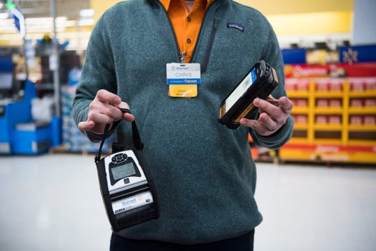 "Walker Springs store manager Chris Rimmer shows off the mobile checkout scanner and card reader used as part of the ""Check Out With Me"" feature Friday, Jan. 25, 2019."